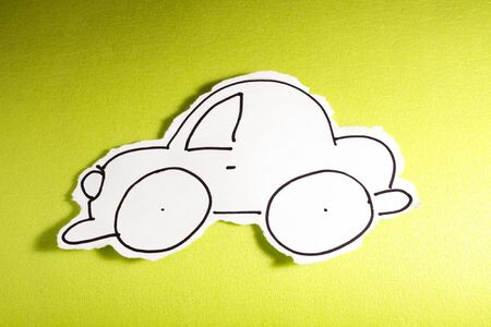 drawed: SKETCH made by a child, little car drawed on a cut out white piece of paper shot on a bright green