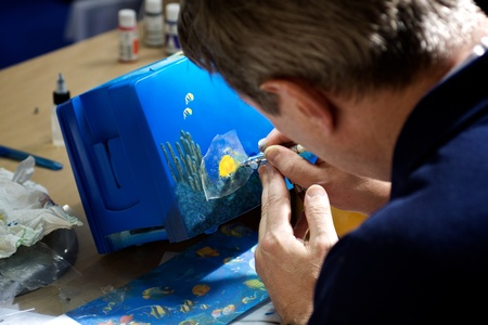 Bologna, Italy - March 10th, 2011: Bricolage demonstration - An artist is painting with the airbrush tool a deep blu undersea landscape with fish and kelp.