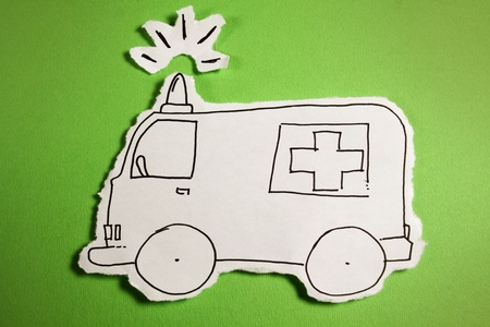 SKETCH made by a child, little Emergency car (ambulance) draw on a cut out white piece of paper shot on a bright green background Stock Photo