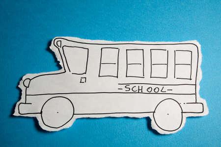 autobus escolar: Boceto hecho por un ni�o, peque�o autob�s escolar se basan en un corte hoja blanca de papel disparo en un brillante fondo azul cian Foto de archivo