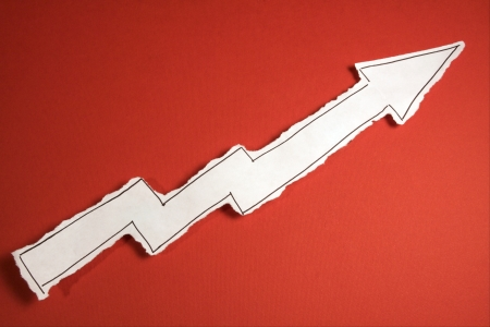 SKETCH made by a child, little Rising Arrow draw on a cut out white piece of paper shot on a bright red background Stock Photo