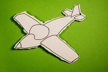 paper cut out: SKETCH made by a child, little Airplane draw on a cut out white piece of paper shot on a bright green background