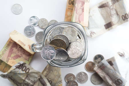 scatter: Rupiah Coin inside of Jar with money scatter around the jar