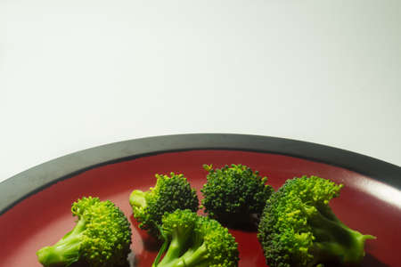 brocolli: Green Brocolli on Red and Black Plate on White Background