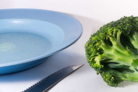 brocolli: Tabletop  of Knife and Plate and Vegetable of Brocolli on white Background Stock Photo