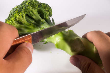 preperation: Brocolli Cut With Knife Holded by person on White Background Look like Preperation of Cooking Stock Photo