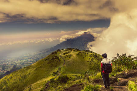 unrecognisable people: Man on Mountain Peak Watching the Natural View of Mount  Merbabu Indonesia