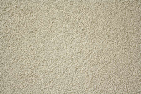 Yellow roughcast wall and peeling paint for texture or background photo