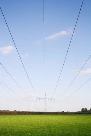 Electricity pylon in a green field photo