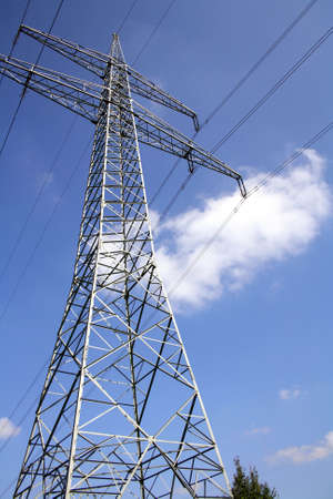 Electric pylon with the wires in front of blue sky with white clouds