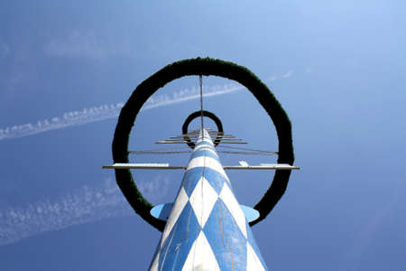 A close up view looking up at a blue and white Bavarian maypole photo