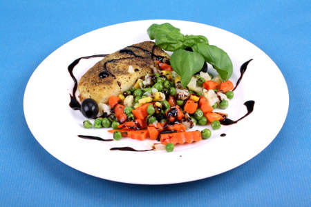 Fisch with buttered vegetables, balsamic cream and basil photo