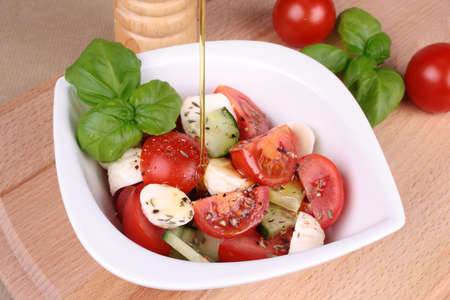 Tomato mozzarella salad with olive oil, basil and cucumbers Imagens