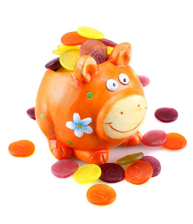 christmas savings: Orange piggy bank with colorful money on white background