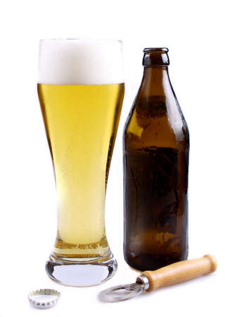 Light beer in glass with brown bottle and bottle opener photo