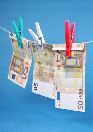 Money laundering from fifty euro notes on a blue background photo