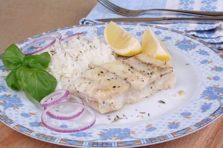 tilapiini: Fish fillet with rice, lemon and onion slices split