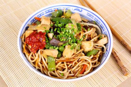 Kina pan med ätpinnar på bambu bakgrund