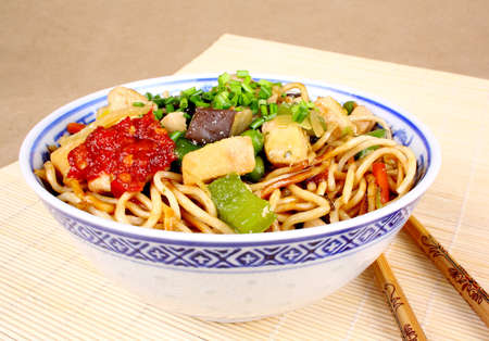 Asian fried noodles with chopsticks on Bamboo Saucer photo