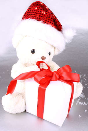White teddy bear in Santa hat with gift on a silver background