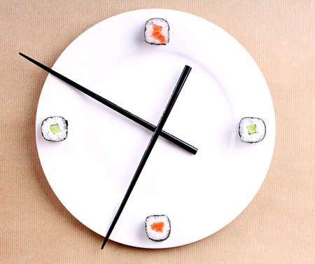 Sushi time in the form of a wall clock on a brown background photo