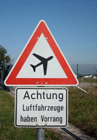 risiko: Warnung Schild vor Flugzeuge am blauen Himmel im Hintergrund