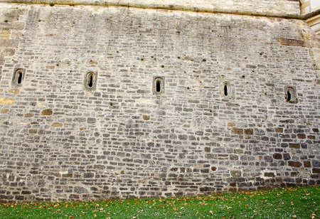 loophole: Old brick wall with five loophole as background