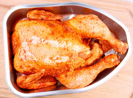 Uncooked whole marinated chicken in aluminum foil tray photo
