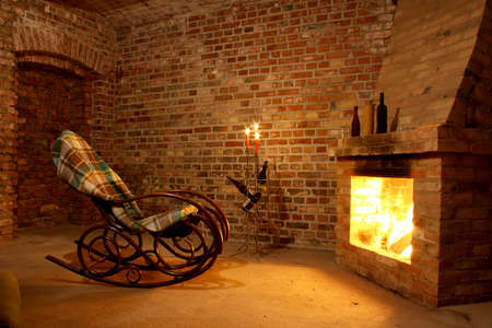 Rocking chair by the fireplace in brick room with candles photo