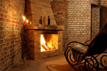 Rocking chair by the fireplace in brick room and candles Imagens