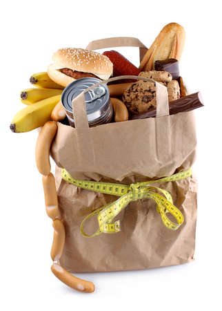 Paper shopping bag with high-calorie foods and measuring tape isolated photo