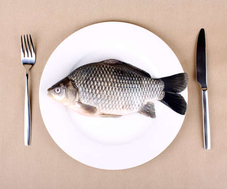 Fresh fish carp on a white plate with cutlery photo