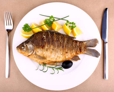Fried fish on white plate with fork and knife, closeup photo