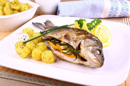 Whole grilled fish served with potatoes, sauce and lemon photo