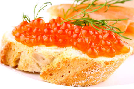 Red caviar on bread with dill on white plate closeup photo