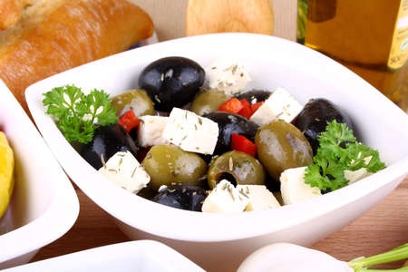 Green and black olives with feta cheese, closeup photo