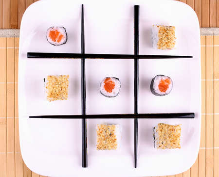 Tic tac toe from Sushi and chopsticks, top view photo