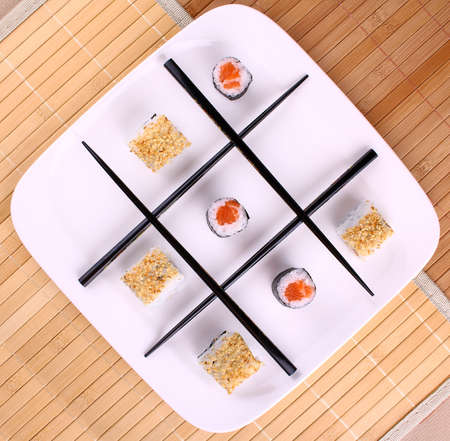 Tic tac toe play and chopsticks with sushi, top view