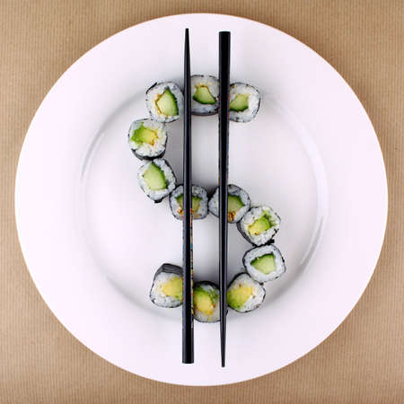 Maki sushi as dollar sign on white plate, top view photo