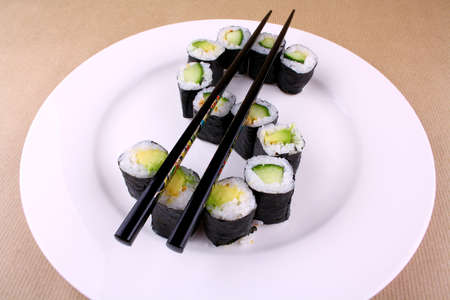 Sushi with chopsticks as a dollar sign on white plate photo