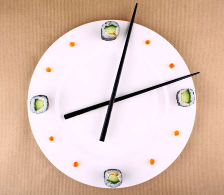 Time Concept with sushi on white plate, top view