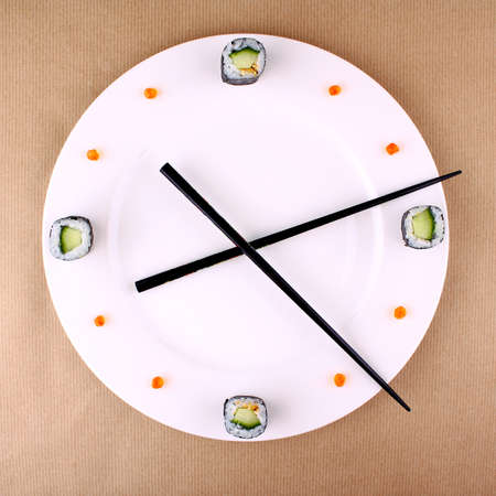 Clock Concept with sushi on white plate, top view photo