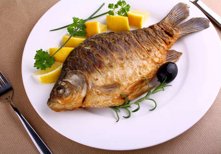 Fried fish on white plate with knife and fork, closeup photo