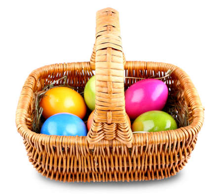 Wicker basket with colorful Easter eggs, isolated photo