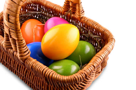 Wicker basket with colorful Easter eggs, close up photo