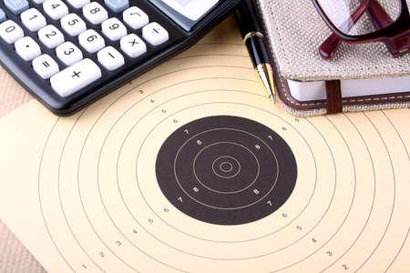 Setting goals - target, calculator, pen, notebook, glasses photo