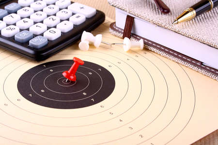 Hit the target - target, red pin, calculator, pen, notebook