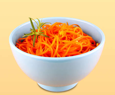Carrot salad in blue bowl on yellow background, isolated