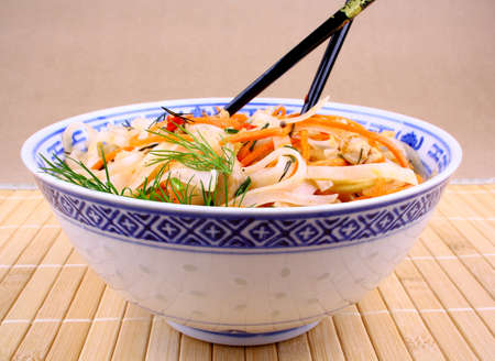 Rice noodle with chicken meat and chopsticks, close up