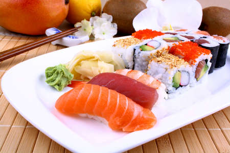 Appetizing sushi with wasabi, fruits and chopsticks closeup